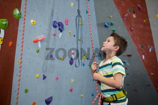 Boy preparing for rope climbing in fitness studio