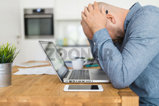 Unhappy man working from his home during the pandemic