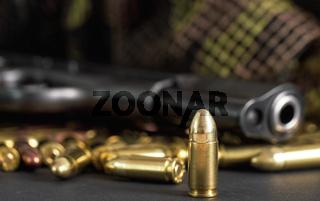 Single yellow brass bullet detail, black metal gun in background