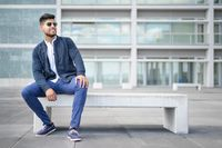 Portrait of young man in stylish sunglasses posing while sitting in bench in urban background.