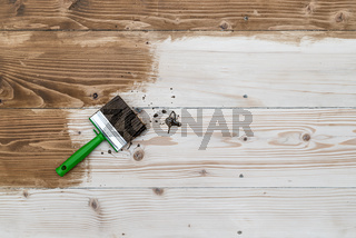 Square cut brush on wooden floor made with softwood boards, top view. Toning floor with wood stain, emphasizing the texture. Decoration process. Stage before varnishing.