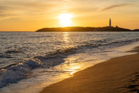 Peaceful sunset on the Playa de Maria Sucia Beach with the Cape Trafalgar Lighthouse in the background