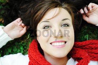 Young beauty girl laying on autumn ground and leaves, perfect face and natural white healthy teeth, fashionable fall clothes