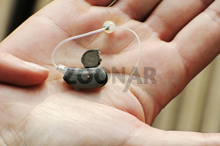 Modern small hearing aid in the palm of a woman