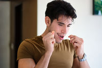 Young man using dental floss cleaning teeth