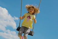 Child swings high. With blue sky background.
