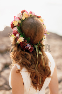Bride with a wreath of roses on her head, back view. A flower wreath on the head of a girl for brown hair.