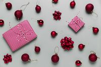 Gray background with two pink Christmas gift boxes, red ball toys, spheres, bows