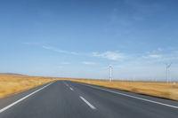 empty road through grassland view and wind farm