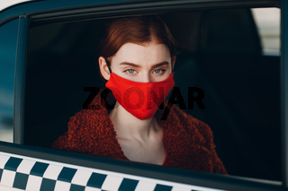 Young woman passenger takes a ride by taxi car during the coronavirus pandemic quarantine. Woman wearing sterile medical face mask. Social distance and health safety in transportation concept.