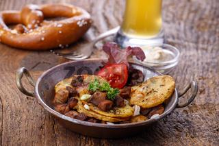Kartoffelgröstl auf dunklem Holz