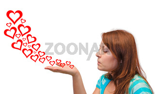 Young woman blowing hearts