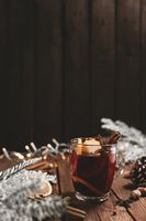 Glass cup of Mulled Wine on wooden table and background. Christmas time concept