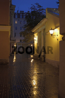 A yard with street lamps and stone pavement at evening in Saint Petersburg