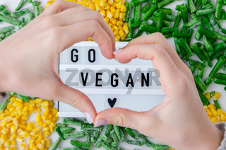 Lightbox with text GO VEGAN frozen vegetables food of yellow corn, green beans. Harvest Food preservation for winter.