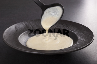 Pouring cream soup in trendy dark plate.