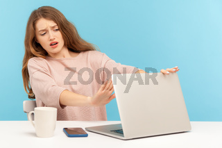 Emotional young woman working on laptop on blue background.
