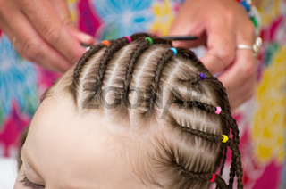 Hairdresser hands weaving a pigtails