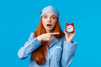 Shocked and concerned, worried cute redhead girl pointing at alarm clock with frustrated, nervous expression, being late, dont know how set up right time, standing blue background in nightwear