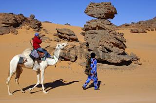 Tuareg Nomade führt ein Dromedar mit einer Touristin durch die Wüste