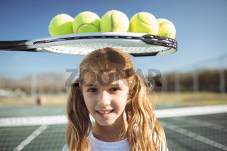 Smiling girl standing below tennis racket and balls