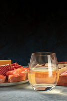 A glass of white wine with salmon sandwiches and cheese, a side view