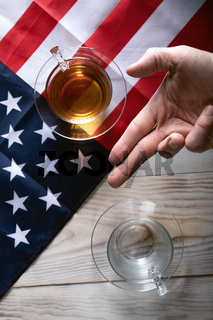 Table separated by American flag with full cup and empty cup on table and man's hand in V position