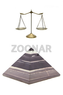 isolated brown stone pyramid and golden scale on white
