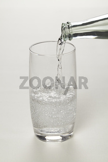 Trinkglas mit Mineralwasser beim Einschenken
