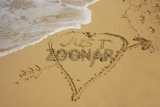 'Just married' written in sand on a beach