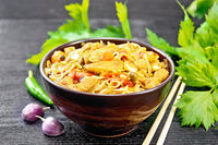Noodles with cabbage and chicken in bowl on wooden board