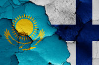 flags of Kazakhstan and Finland painted on cracked wall