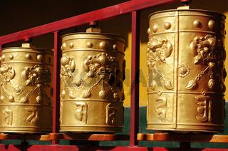 Golden Tibetan prayer wheels in a lamasery