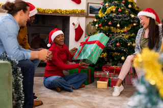 Happy diverse female and male friends sharing presents at christmas time