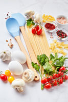 Food background with different kinds of pasta, tomatoes, herbs, mushrooms, eggs, seasonings scattered on light marble background, top view.