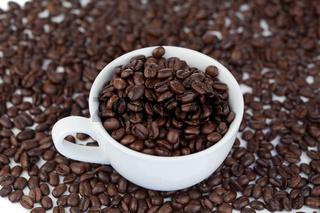 Small white cup of coffee with coffee beans
