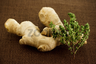 Ginger and thyme on brown cloth