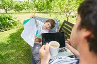 Alleinerziehender Vater am Computer mit Sohn im Garten