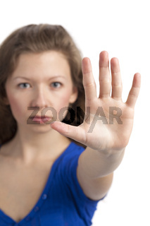 Streng blickende junge Frau mit Hand zum Halt erhoben