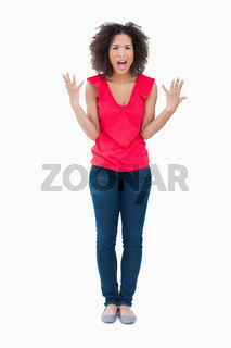 Upset brunette woman raising her arms