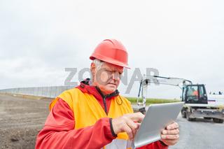 Bauleiter mit Tablet Computer auf der Baustelle