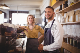 Portrait of smiling young waiter and waitress standing by espresso maker