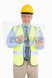 Man in vest and with helmet holding pane