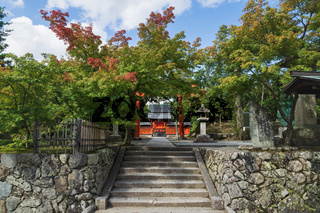 Entrance with torri gate sourrounded by maple trees at the temple Hachiman Daibosatsu in Arashiyama, Kyoto, Japan