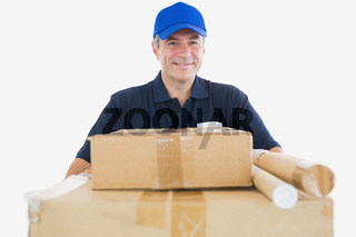 Happy mature courier man carrying cardboard boxes