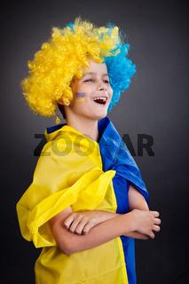 Football fan with  ukrainian flag on a black background