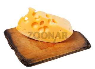 Piece of cheese on old wooden board