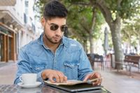 Young traveller man sitting in a cafe terrace and planning her trip with map and laptop