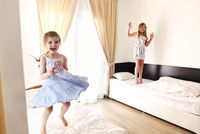 Two cute carefree little sisters girls in casual clothes playing having fun in childrens room