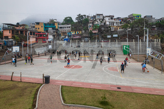 Local men playing football and basketball on the sports field along the town houses in Santiago Atitlan, Guatemala